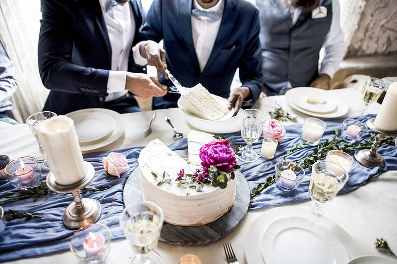 same-sex couple cutting wedding cake