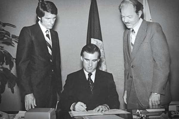 John V. Stevens (right) watches as Governor Jerry Brown signs legislation