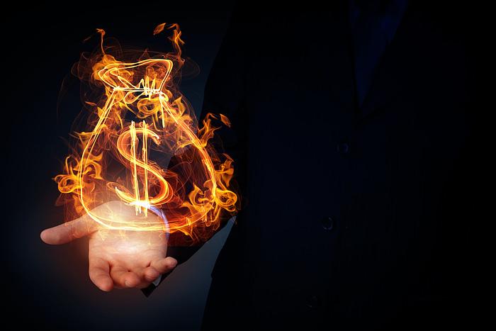 Burning dollar sign in businessman palm on dark background